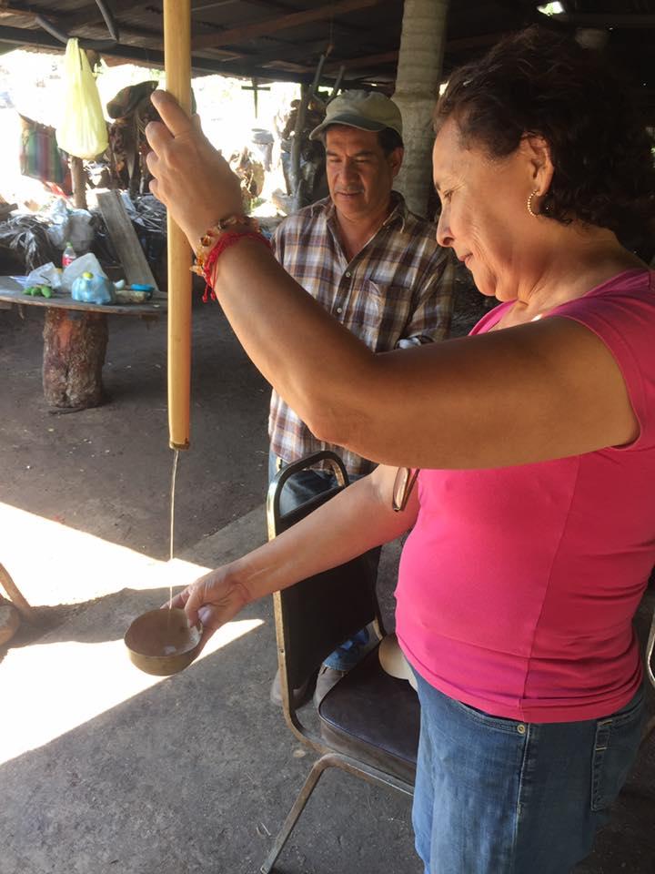Mujer venenciando mezcal